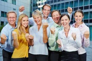 Jubelndes Business Team mit geballten Fäusten draußen vor dem Büro
